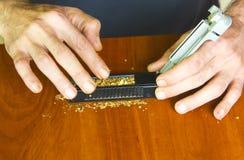Cigarettes de roulement d'homme utilisant le tabac frais Photographie stock