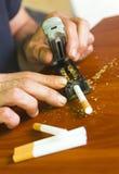 Cigarettes de roulement d'homme utilisant le tabac frais Photo stock