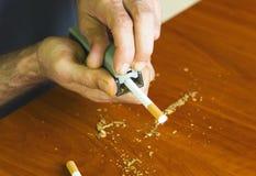 Cigarettes de roulement d'homme utilisant le tabac frais Images stock