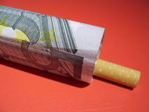Cigarettes are expensive. Cigarette and money Royalty Free Stock Photography