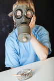Cigarettes in front of sad child in gas mask Stock Photography
