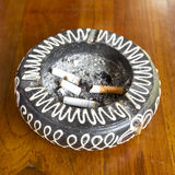 Cigarettes fumées dans le cendrier blanc Photos stock