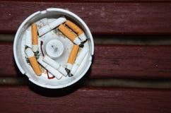 Cigarettes fumées dans le cendrier blanc sur la table en bois Photo stock