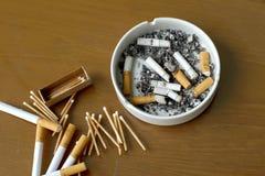 Cigarettes fumées dans le cendrier et l'allumette blancs Photos stock