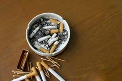 Cigarettes fumées dans le cendrier et l'allumette blancs Photo libre de droits