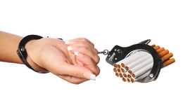 Cigarettes and handcuffs on female hand isolated Royalty Free Stock Photo