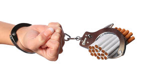 Cigarettes and handcuffs on female hand isolated on white Stock Photography