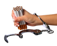 Cigarettes and handcuffs on female hand isolated on white Royalty Free Stock Photos