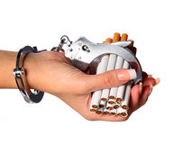 Cigarettes and handcuffs on female hand isolated Stock Photography