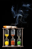 Cigarettes on hourglasses. Two cigarettes burning over hourglasses Royalty Free Stock Image