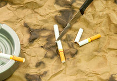 Cigarettes and knives Stock Images