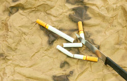 Cigarettes and knives Stock Photography