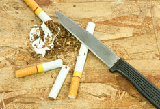 Cigarettes and knives Royalty Free Stock Images