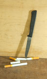 Cigarettes and knives Royalty Free Stock Photography