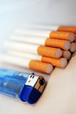 Cigarettes and Lighter. A photograph of a pile of cigarettes and a blue cigarette lighter Royalty Free Stock Photography