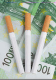 Cigarettes lying on the bills. Three cigarettes lying on the bills of one hundred euros Royalty Free Stock Image