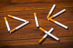 Cigarettes lying on wooden surface shaped into the word die, artistic anti smoking concept Royalty Free Stock Photography