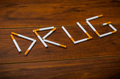 Cigarettes lying on wooden surface shaped into the word drug, artistic anti smoking concept Royalty Free Stock Image