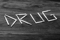 Cigarettes lying on wooden surface shaped into the word drug, artistic anti smoking concept, black and white edition Royalty Free Stock Image