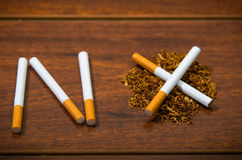 Cigarettes lying on wooden surface shaped into the word no, artistic anti smoking concept Royalty Free Stock Images