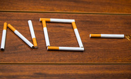 Cigarettes lying on wooden surface shaped into the word no, artistic anti smoking concept Stock Photography