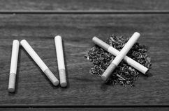 Cigarettes lying on wooden surface shaped into the word no, artistic anti smoking concept, black and white edition Stock Images