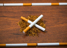 Cigarettes lying on wooden surface shaping into crossed lines, tobacco spread around, seen from above Stock Photo