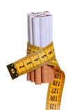 Cigarettes with measure tape Royalty Free Stock Image