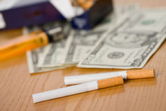 Cigarettes and money Royalty Free Stock Photography