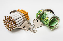 Cigarettes and money with handcuffs - cost of smoking. Cigarettes and money with handcuffs as a concept of smoking cost Stock Photography