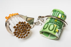 Cigarettes and money with handcuffs - cost of smoking. Cigarettes and money with handcuffs as a concept of smoking cost Royalty Free Stock Photos