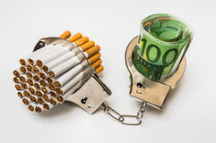 Cigarettes and money with handcuffs - cost of smoking. Cigarettes and money with handcuffs as a concept of smoking cost Royalty Free Stock Photo