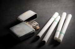 Cigarettes with old metal lighter. Royalty Free Stock Photo