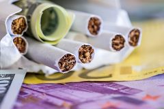 Cigarettes in a pack on the dollar and euro. Banknotes Royalty Free Stock Photos