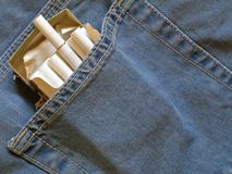 Cigarettes pack within pocket. Cigarettes pack within back pocket of blue jeans stock photography