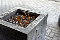 Cigarettes in a public ashtray Royalty Free Stock Images