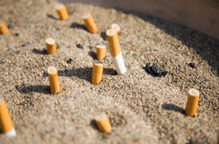 Cigarettes in sand Royalty Free Stock Photos