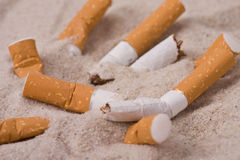 Cigarettes in sand Stock Photography