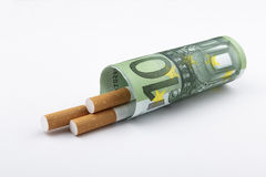 Cigarettes smoking concept. Cigarettes smoking concept, a 100 Euro bill wrapped around 3 cigarettes Royalty Free Stock Photo
