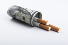 Cigarettes smoking concept. Cigarettes smoking concept, a 100 US dollar bill wrapped around 3 cigarettes Royalty Free Stock Photo