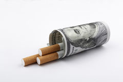 Cigarettes smoking concept. Cigarettes smoking concept, a 100 US dollar bill wrapped around 3 cigarettes Stock Images