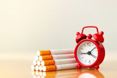 Cigarettes stack and red alarm clock. World no tobacco day. Cigarette and family figure. royalty free stock photo