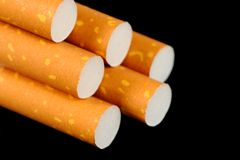 Cigarettes with Yellow Filters on Black Background Royalty Free Stock Image