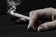 cigaretthand som rymmer den gammala kvinnan Arkivfoton