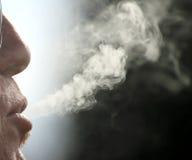 Cigarettrök kommer ut ur munnen av rökaremannen Royaltyfria Bilder