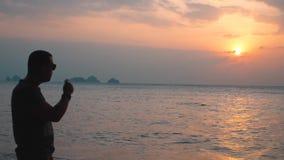Cigarr för mankonturrök med havssikt på solnedgången arkivfilmer