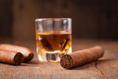 Cigarrer och whisky på den gamla trätabellen royaltyfri fotografi