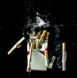Cigarretes splashing into water Stock Images