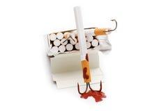 Cigarrillo con un gancho de pesca Foto de archivo libre de regalías