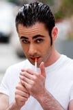 Cigarrillo de la iluminación del hombre Foto de archivo